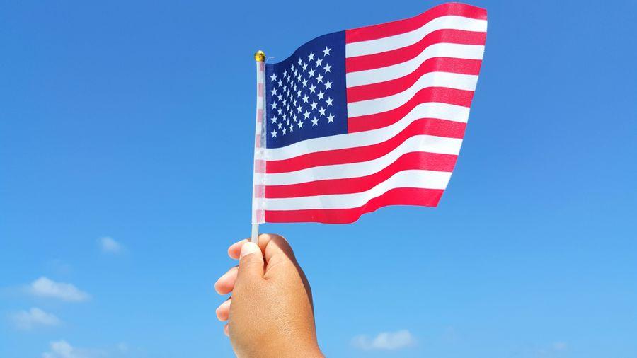 Human Hand Using American Flag Against Sky