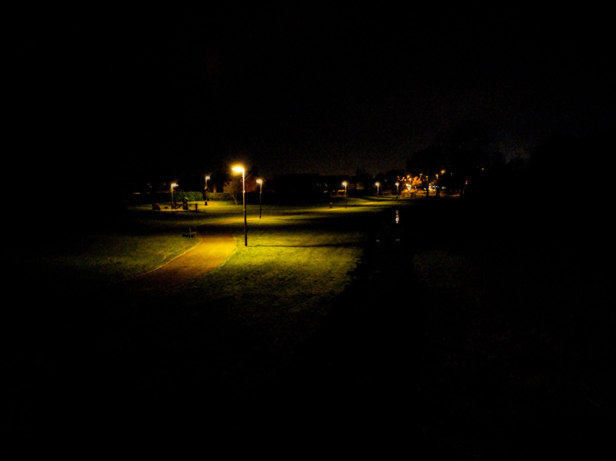 illuminated, night, copy space, no people, lighting equipment, sky, nature, dark, architecture, outdoors, built structure, building exterior, street light, street, grass, transportation, field, tranquility, city, building