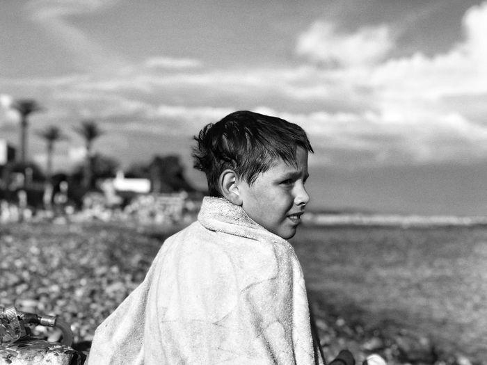 Portrait of boy on beach against sky