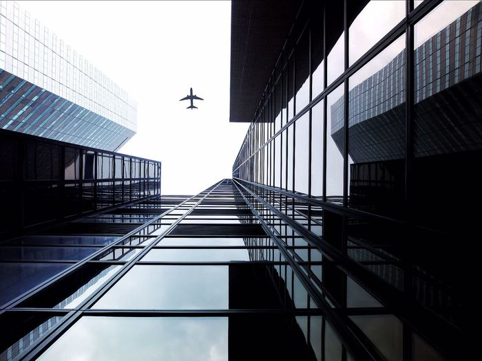 Low angle view of airplane in flight and tall building
