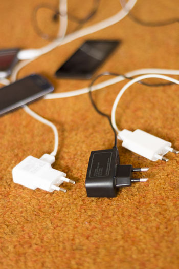Close-up of mobile phone and chargers on table