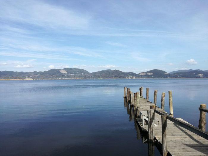 Wooden pier in lake against sky