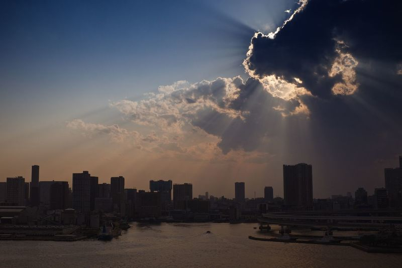 Sunbeam on city and bay against sky during sunset