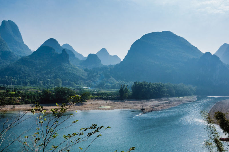Scenic view of river with mountain range in background