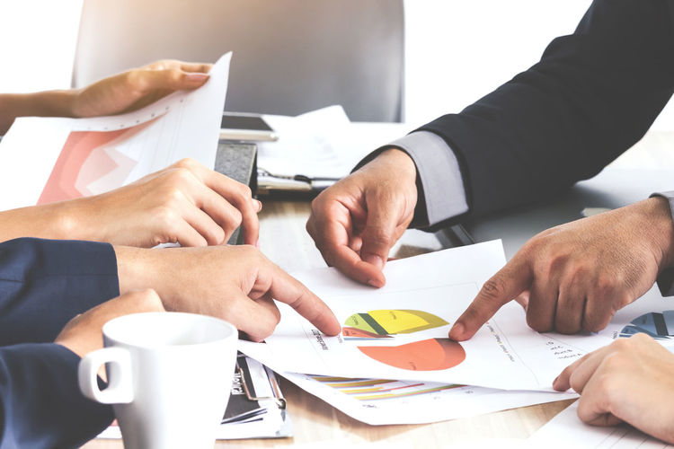 Cropped image of business people discussing at desk in office