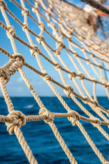 Close-up of rope net against sea and sky