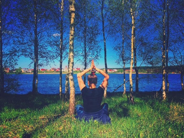 Rear View Of Woman Meditating While Sitting On Grassy Field By Lake In Forest