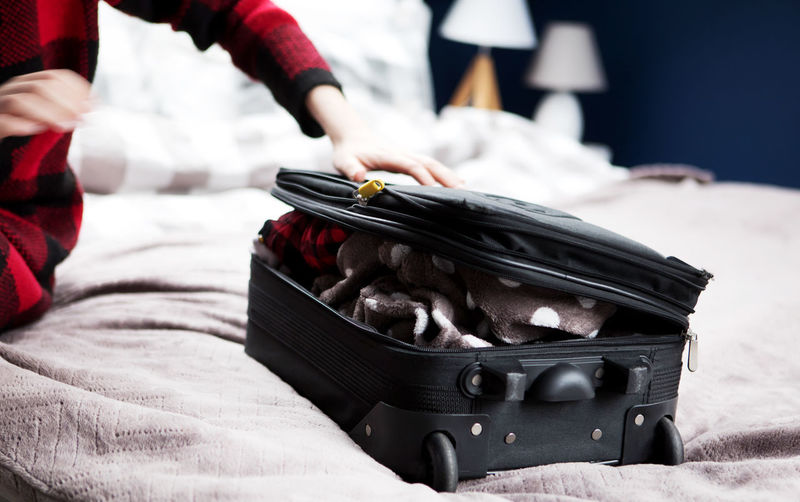 Cropped hand closing suitcase