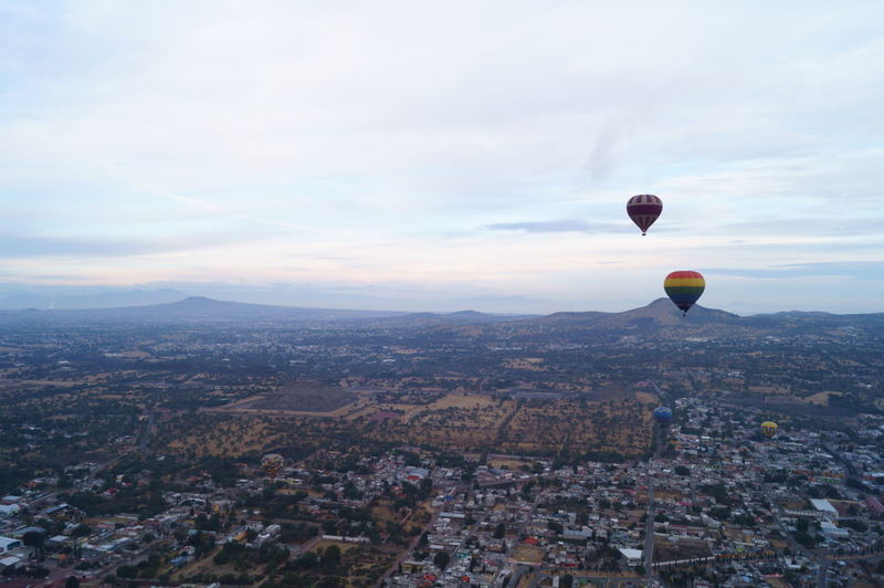 Hot air balloons flying over cityscape against sky