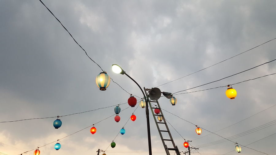 Low angle view of illuminated lanterns hanging on cables against cloudy sky