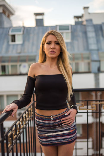 Portrait Of Sensuous Young Woman Standing On Balcony In City