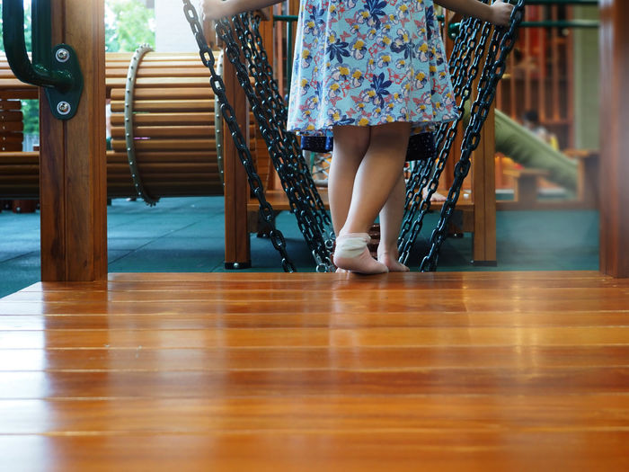 Closeup of girl feet walking and playing on the children playground. selected focus.
