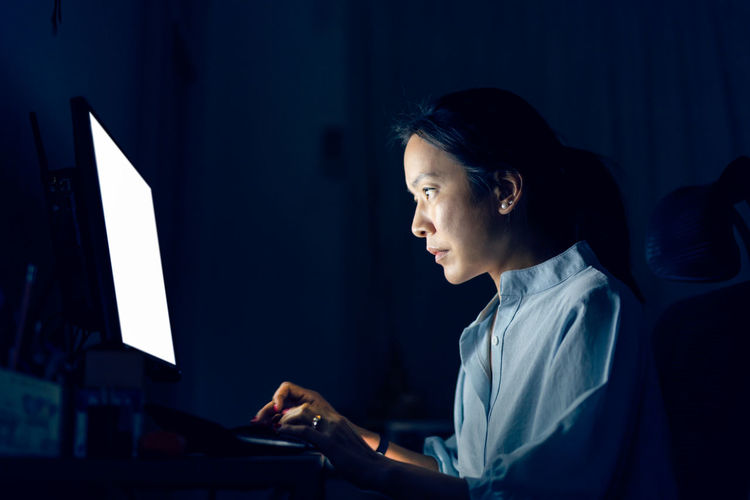 Side view of woman typing on keyboard computer