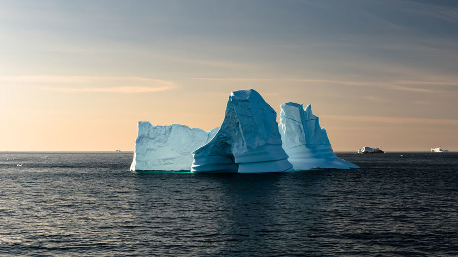 Iceberg In Sea Against Sky During Sunset