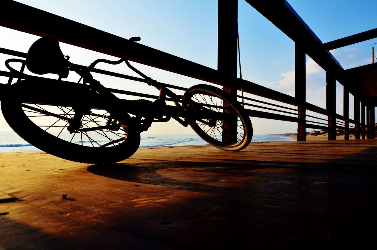 BICYCLE PARKED ON WOODEN RAILING
