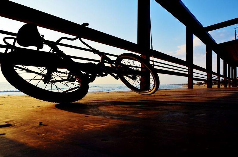 Bicycle wheel on wooden floor against sky