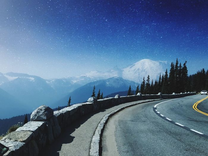 Road amidst snowcapped mountains against sky
