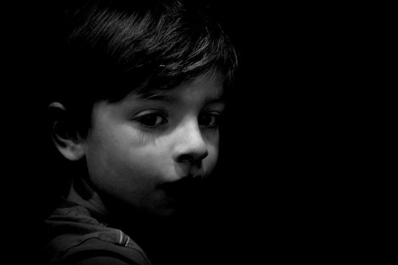 Close-up portrait of cute boy against black background