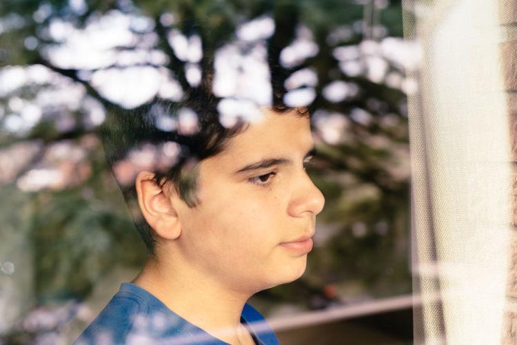Teenage boy looking through window
