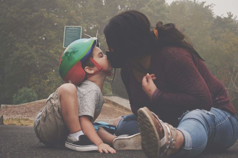 Mother wearing mask kissing son sitting on road