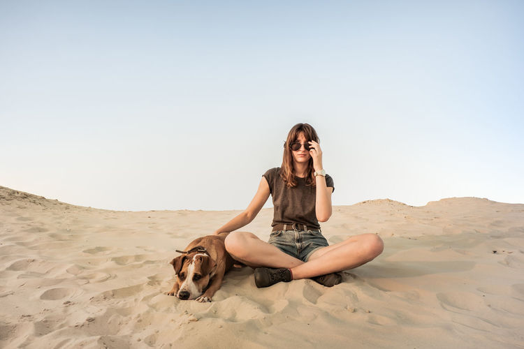 Animal Animal Themes Beach Beautiful Woman Canine Clear Sky Dog Domestic Domestic Animals Front View Land Leisure Activity Mammal Nature One Animal One Person Outdoors Pets Real People Sand Sky Young Adult