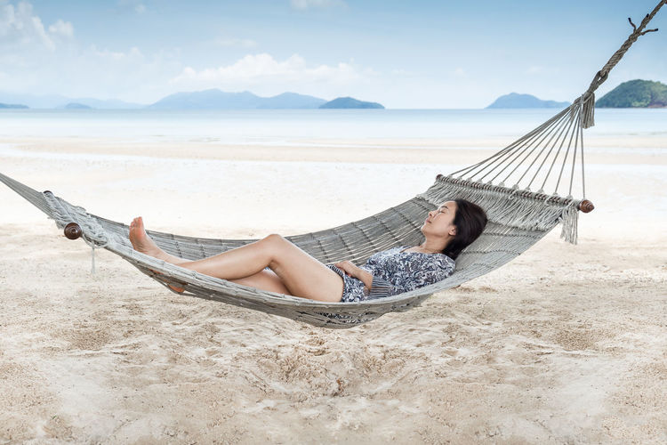Woman relaxing on hammock at beach against sky