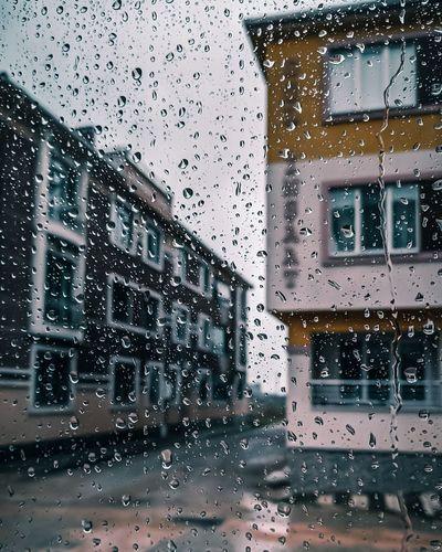 Buildings seen through wet glass window during rainy season