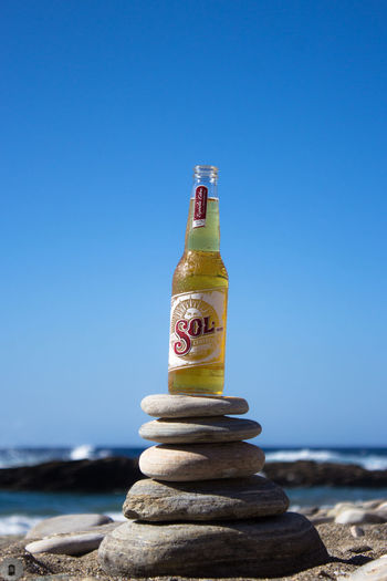 Sol beer on a stone tower in Icaria Island, Greece. Ballance Beach Beer Beer Bottle Beer Time Beers Bottle Close-up Commercial Greece Ikaria Ikaria Greece Ikariagram Sand Sea Sol Sol Beer SolBeer Stone Stone Balancing Stones Tower