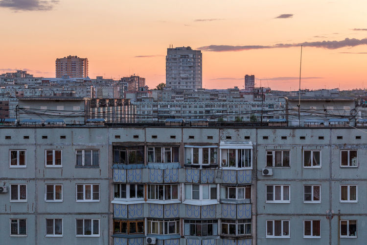 Windows, roofs and facade of an apartment building in russia at evening