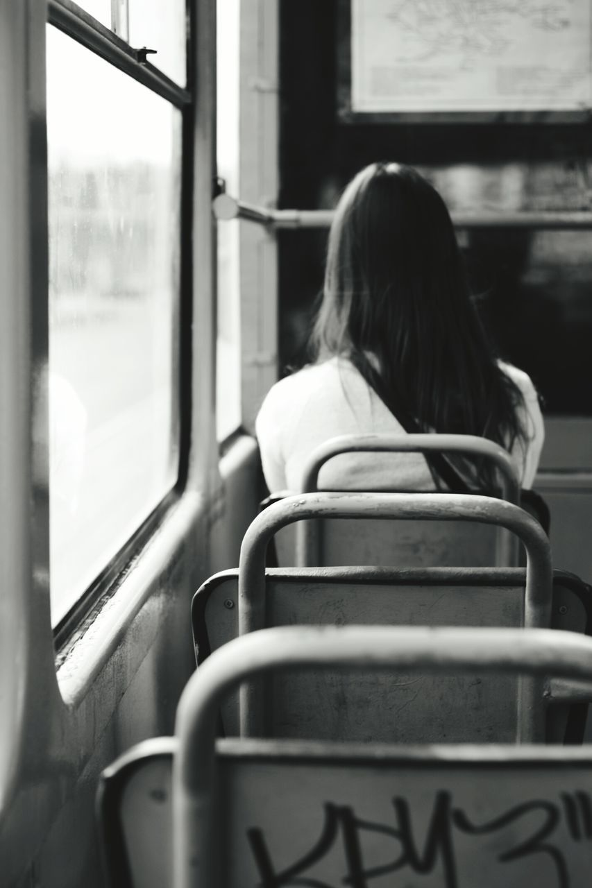 rear view, real people, public transportation, transportation, one person, train - vehicle, day, lifestyles, sitting, indoors