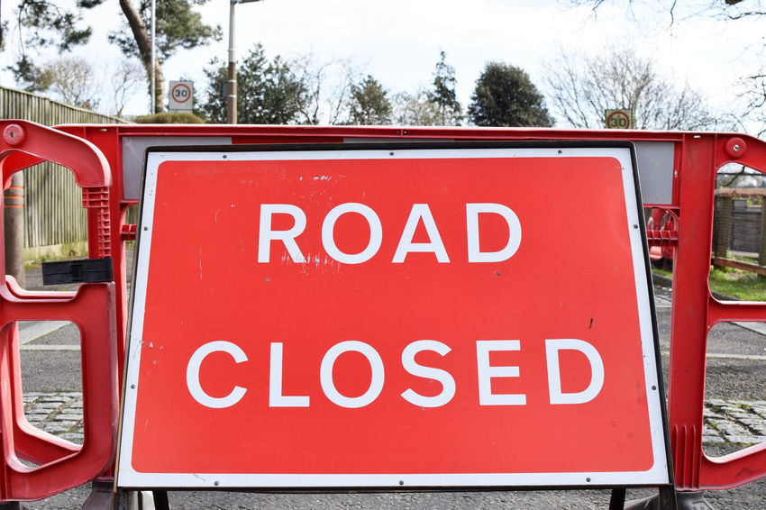 Road Closed Capital Letter Close-up Communication Day Information Information Sign Land Vehicle Mode Of Transportation Nature No People Outdoors Plant Public Transportation Red Road Closed Road Closed Sign Road Closure Road Sign Sign Text Transportation Tree Warning Sign