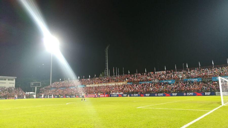 Illuminated soccer field against sky at night