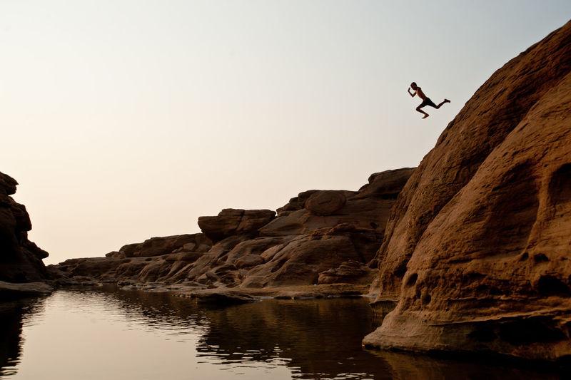Man diving in lake against sky