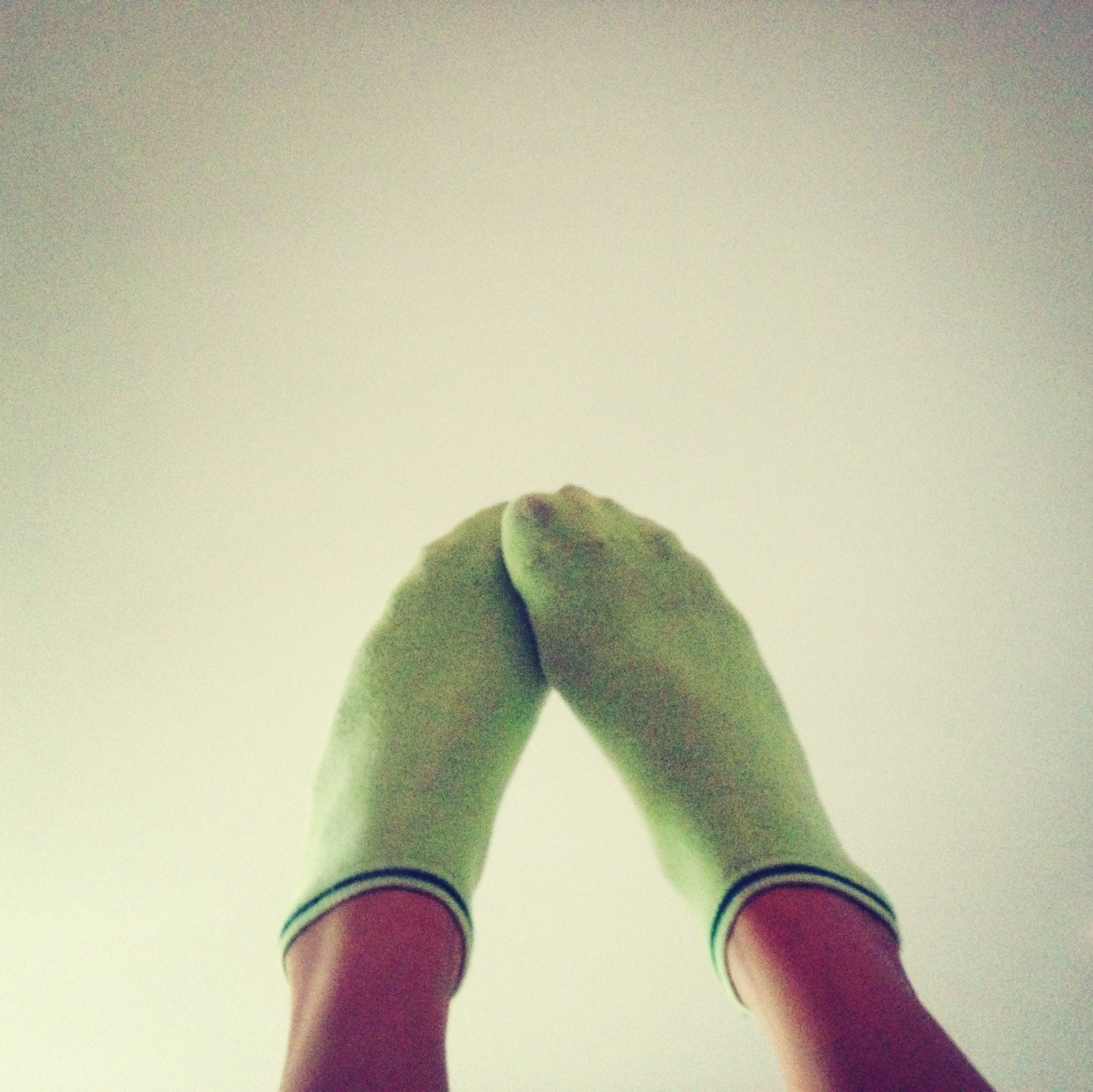part of, personal perspective, person, close-up, cropped, copy space, shoe, low angle view, low section, green color, unrecognizable person, indoors, holding, human finger, studio shot, day