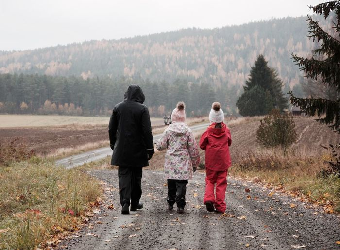 Rear view of mother with daughters on footpath