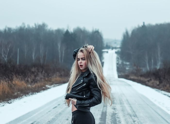 Young woman posing while standing on snow covered road