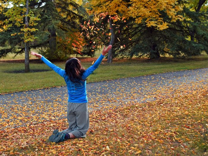 Full length of person with arms raised in park during autumn