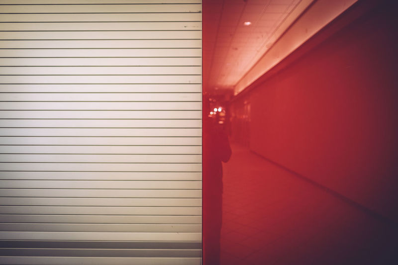 Reflection Of Person On Red Wall In Shopping Mall