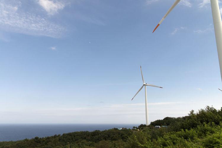 Wind turbines on sea against sky