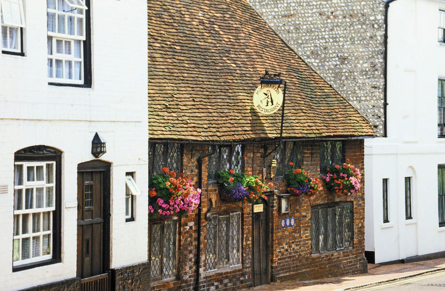A typical street in pretty village of Alfriston, East Sussex, UK Architecture Window Day Outdoors No People Shop Sign East Sussex Hanging Baskets Of Flowers Alfriston Building Exterior Built Structure Red Brick House White Walled Buildings