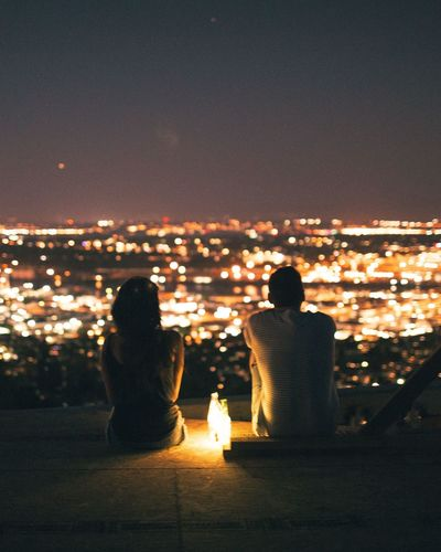 there comes a time even the city sleeps. Adapted To The City Rear View Illuminated Couple - Relationship Night Sea Relaxation Togetherness Date Night - Romance Lifestyles Cityscape Women Bonding Heterosexual Couple Two People Leisure Activity Sky Enjoyment Men Sitting