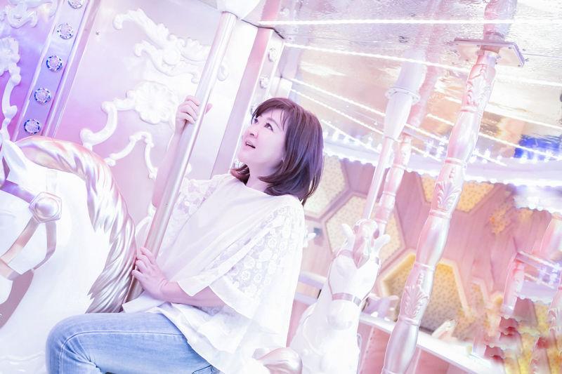 Mature Woman Sitting On Carousel Horse At Amusement Park