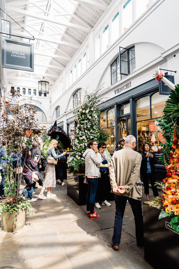 Fleurs de Villes Floral Couture Installation in Covent Garden Market Building. Architecture Built Structure Day Luxury Couture Fashion Blossom Springtime London Uk England Covent Garden  Covent Garden Market Floral Fleurs Landmark Extravaganza Shopping Artist Flower Group Of People Real People Men Adult Women Building Exterior Walking People Lifestyles City Leisure Activity Plant Full Length Street Retail  Crowd Rear View Outdoors Consumerism