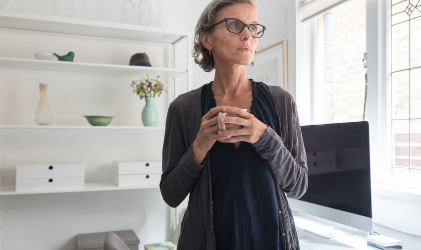 Woman with cup in home office One Person Front View Glasses Eyeglasses  Adult Mature Adult Indoors  Holding Real People Mature Women Women Females Lifestyles Short Hair Business Person Waist Up Looking Casual Clothing Contemplation Wireless Technology
