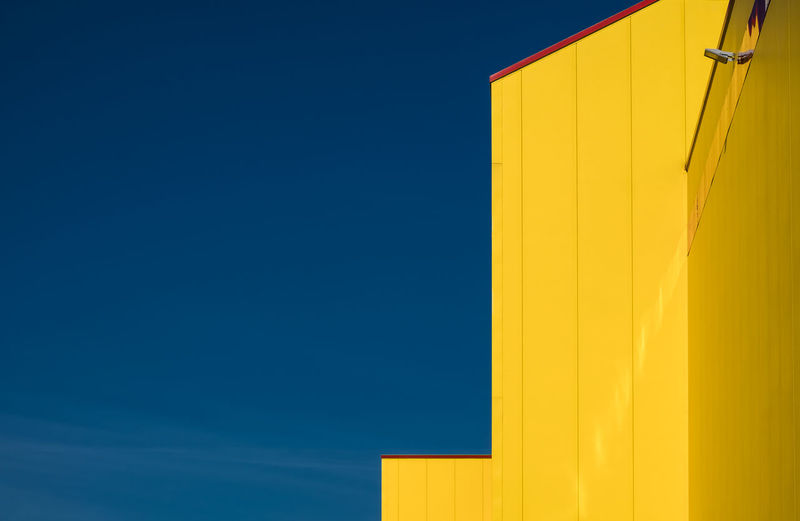 Low angle view of yellow house against clear blue sky
