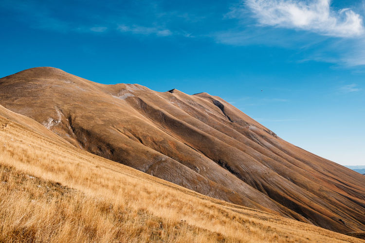 Low angle view of arid landscape against sky in castelluccio, umbria italy