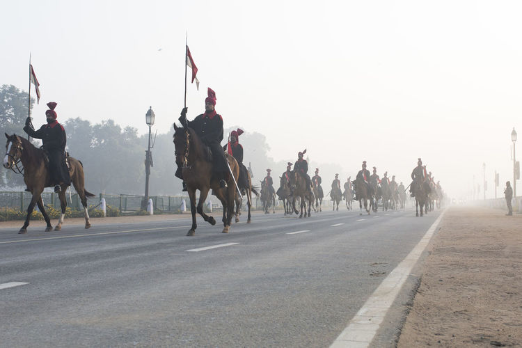 People riding horses on street against clear sky