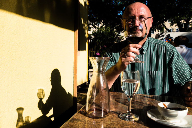 Mature man having red wine at outdoor restaurant on sunny day