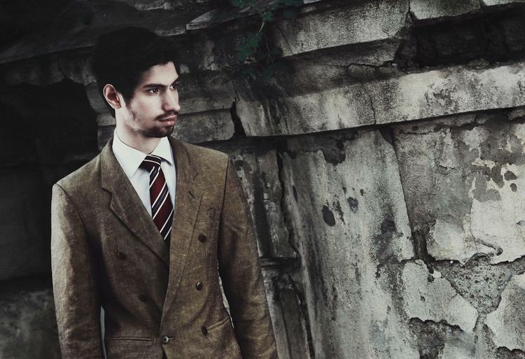 Thoughtful man in businesswear standing by abandoned wall