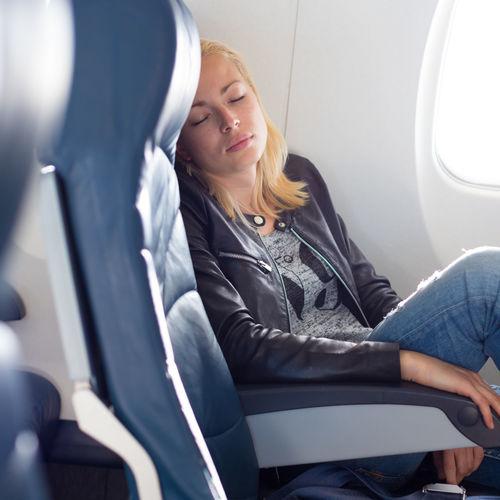 Mid adult woman sleeping at airplane